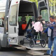 kerekes székest emelnek be a speciális buszba