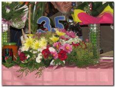 Virágcsokorba tűzött 35-ös kék számok. Két oldalán vázák virágcsokrokkal. Mindez mályvaszínű, kockás abrosszal letakart asztalon.