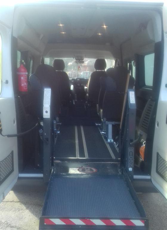 A kisbusz hátuljához illesztett, kerekesszékkel közlekedő embereket a kocsiba emelő szerkezet.