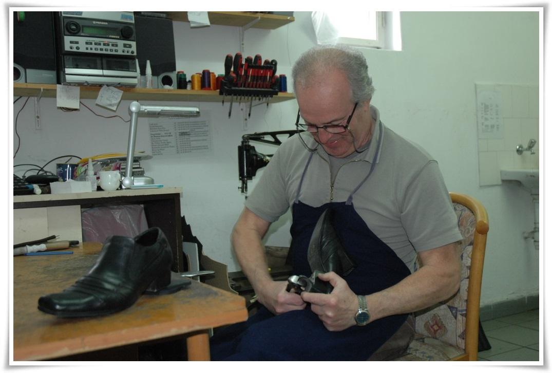 A cipész kezépben a cipővel, mellette a gépparkja.